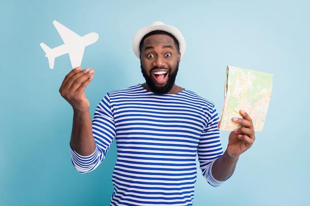 興奮した暗い肌の男の旅行者の写真は紙の飛行機の地図を保持します素敵な安い旅行のバリエーションを提供します低価格は白いサンキャップストライプセーラーシャツ分離された青い色の壁を着用します