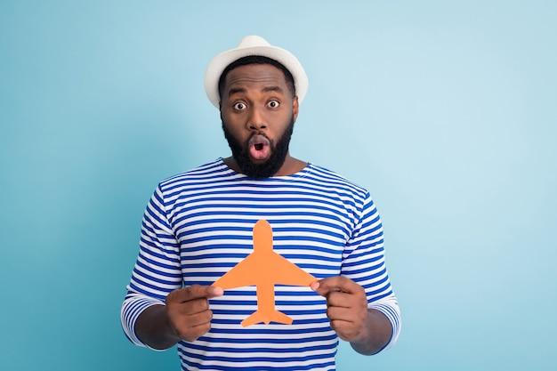 興奮した暗い肌の男の旅行者の写真は紙飛行機を開いて口を開けて宝くじに勝つ海外旅行リゾートウェア白いサンキャップストライプセーラーシャツ孤立した青い色の壁