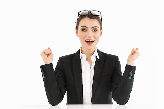 白い壁に隔離されたオフィスの机に座って仕事をしながら正装を着た興奮した女性労働者の実業家の写真