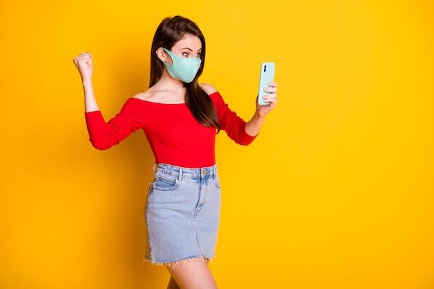Фотография возбужденной девушки в медицинской маске использует смартфон, поднять кулаки, читать новости о победе в социальных сетях, носить короткую мини-юбку с красным верхом, изолированную на ярком блестящем цветном фоне