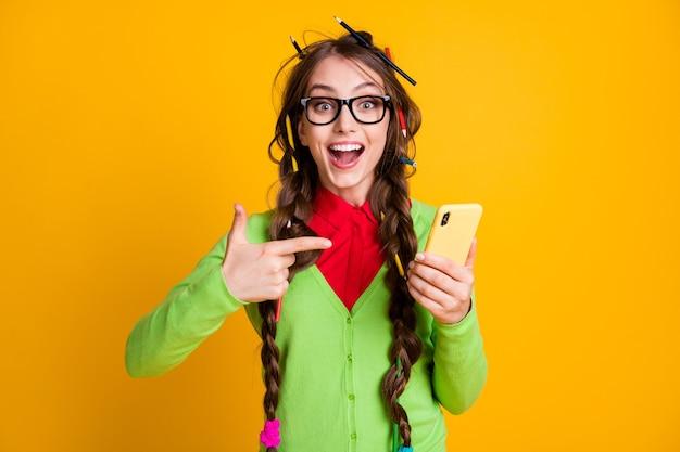 노란색 배경에 격리된 흥분된 소녀의 지저분한 머리 포인트 손가락 스마트폰 착용 셔츠 사진