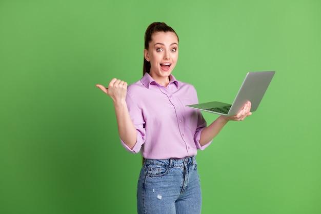 흥분한 소녀 발기인의 사진 원격 노트북 포인트 엄지 손가락 copyspace 와우 소셜 네트워크 광고는 라일락 바이올렛 스타일의 데님 청바지를 입고 녹색 배경을 격리했습니다.