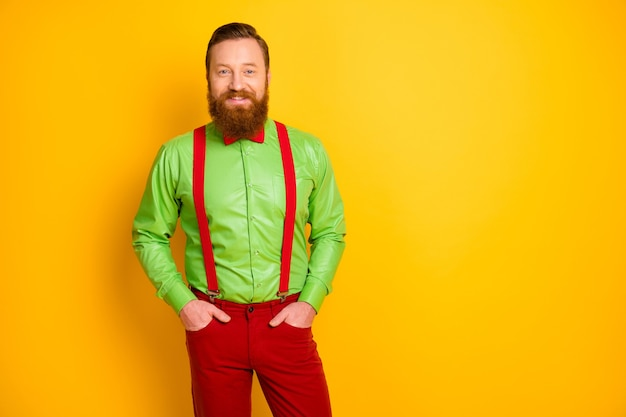 Фото возбужденного счастливого рыжего парня с зубастым улыбающимся элегантным взглядом пришла вечеринка в ярко-зеленой рубашке с красными подтяжками на брюках с галстуком-бабочкой