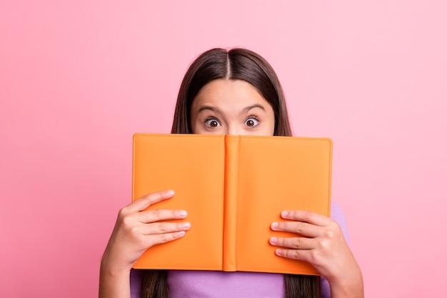 Фотография взволнованной впечатленной малышки скрывает губы фиолетовым джемпером из книжной одежды, изолированным на пастельном цветном фоне