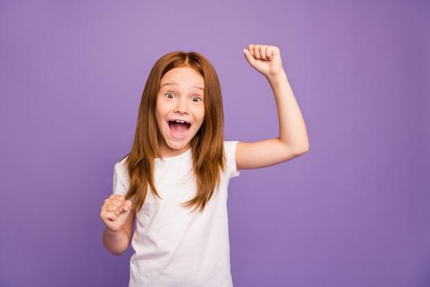 비명을 지르는 주먹을 올리는 흥분된 어린 소녀의 사진