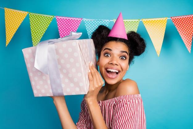 興奮したかなり暗い肌の女性の写真は大きな大きなギフトボックスの誕生日の女の子のパーティーウェアコーンキャップ赤白ストライプシャツ裸の肩を保持しますカラフルな点線の旗は青い壁に掛かっています