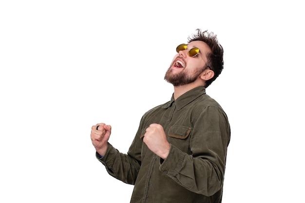 흰색 배경 위에 팔짱을 끼고 축하하는 선글라스를 쓴 흥분한 젊은 남자의 사진