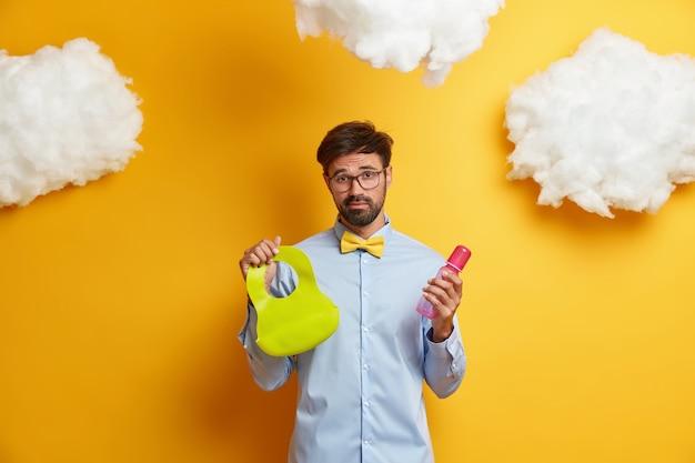 疲れ果てたひげを生やした父親が赤ちゃんを養い、哺乳瓶とよだれかけを持ち、新生児の世話をし、フォーマルな服を着て、白い雲で黄色に対してポーズをとる写真。父権、親の概念 無料写真