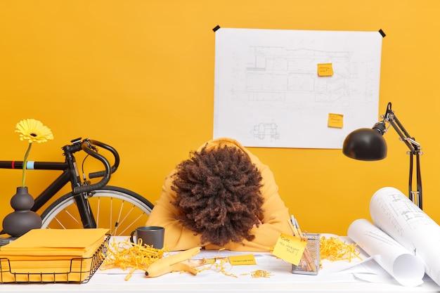 Фотография измученной усталой женщины, опирающейся на стол, весь день работавшей над архитектурным проектом, хочет спать, позирует на рабочем столе с наклейками из скрученных бумажных эскизов. концепция оккупации крайний срок люди.