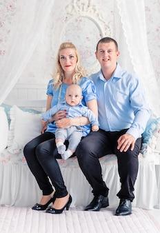 家族の時間の写真。お父さんとお母さんは若い息子と一緒にソファに座っています。