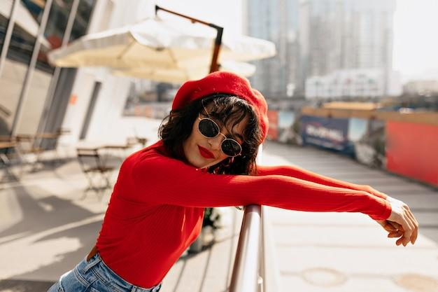 Фотография модной женщины с красивыми каштановыми волосами улыбается
