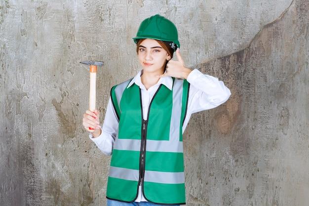 망치를 들고 녹색 헬멧에 여성 건설 노동자의 사진
