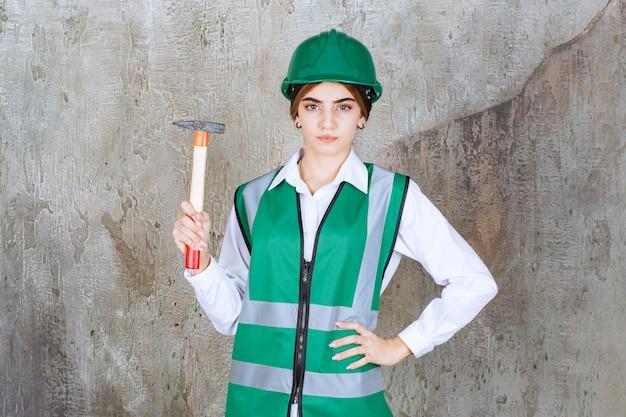 ハンマーを保持している緑のヘルメットの女性建設労働者の写真