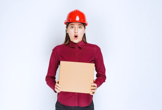 白い背景の上のカートンボックスを保持している赤いヘルメットの女性エンジニアの写真。