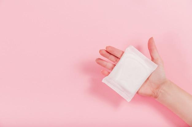 Фото женских рук, держащих гигиеническую прокладку на розовом