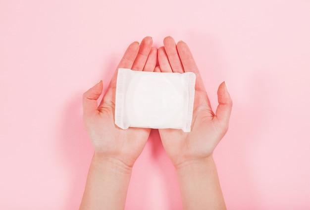 분홍색에 위생 패드를 들고 여성 손의 사진