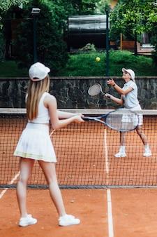 그녀의 파트너가 법정에서 샷을 치는 여자 테니스 선수의 사진.