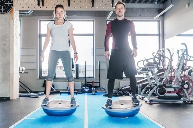 Фотография пары подходят, работающей над мячом bosu в фитнес-студии. вид сзади