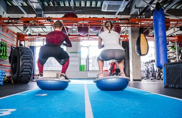 Фотография пары подходят, работающей над мячом bosu в фитнес-студии. выполнение упражнения на корточки