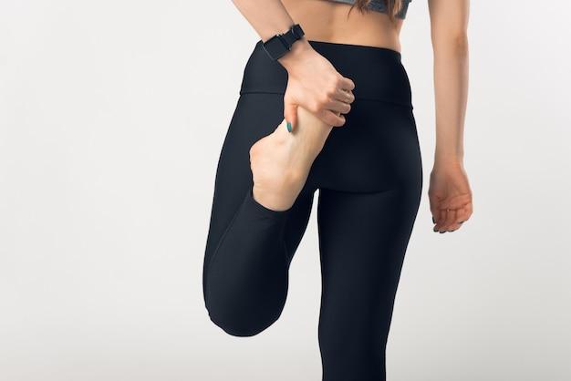 脚にストレッチをするフィットネススポーツ女性の写真