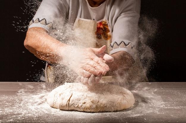 小麦粉と老婆の写真、小麦粉のスプラッシュで祖母の手。調理パン。生地をこねる。暗い背景に分離されました。テキスト用の空のスペース。
