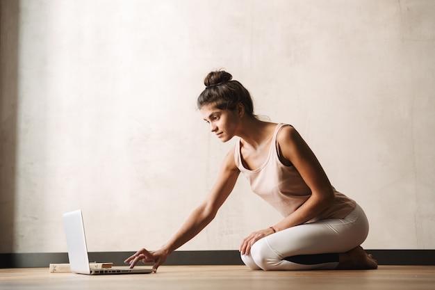 Фотография сосредоточенной красивой женщины в спортивной одежде, печатающей на ноутбуке, сидя на полу дома