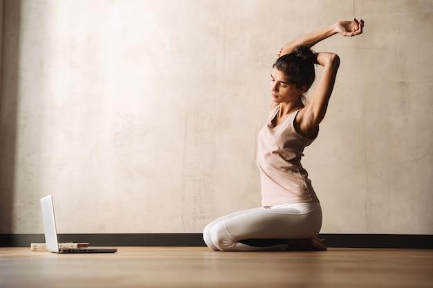 Фотография сосредоточенной спокойной женщины в спортивной одежде, делающей упражнения и использующей ноутбук, сидя на полу дома