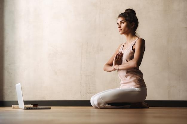 Фотография сосредоточенной спокойной женщины в спортивной одежде, медитирующей с жестом намасте и использующей ноутбук, сидя на полу дома