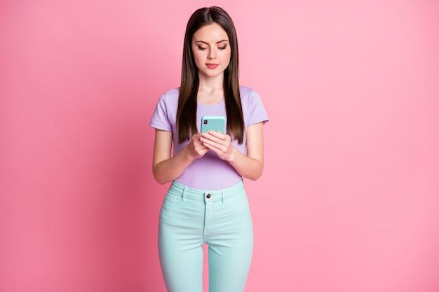 Фотография сосредоточенной девушки, использующей смартфон, следит за информацией в социальных сетях, носит красивый фиолетовый наряд, изолированный на пастельном цветном фоне