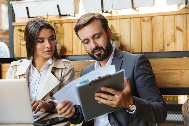 Фотография сосредоточенных офисных работников, мужчина и женщина в формальной одежде, глядя на документы, используя ноутбук и мобильный телефон в кафе