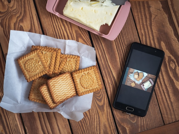 電話での写真のために木製トレイのフードブロガークッキーによって電話で撮られた食べ物の写真