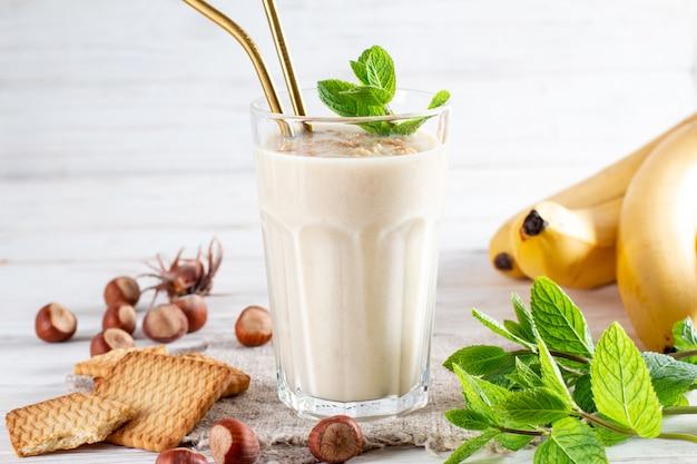 Фото свежего сделанного бананового смузи на деревянном столе с печеньем и бананом. молочный коктейль. белковая диета. концепция здорового питания, место для текста.