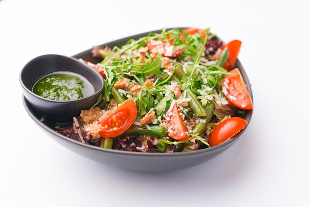 白い表面にビタミンがたっぷり入った新鮮なビーガンサラダの写真