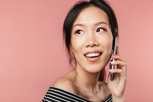 기본 복장을 한 친절한 아시아 여성이 빨간 벽에 격리된 스마트폰으로 웃고 이야기하는 사진