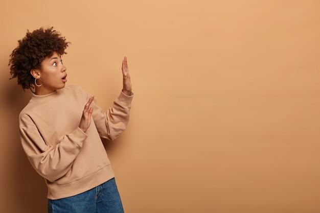 おびえた感情的な女性の写真は横向きになり、防御ジェスチャーで手のひらを上げ、怖い表情で見つめ、目が飛び出します