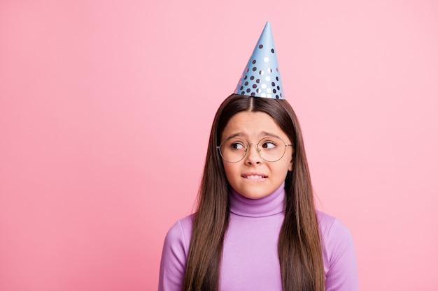 Фотография испуганной маленькой девочки с фиолетовым джемпером на фоне пастельных тонов.