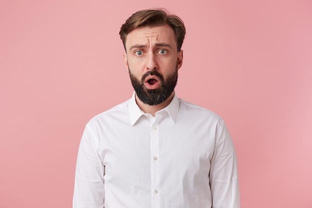 白いシャツを着て、眉をひそめている魅力的なぼんやりしたひげを生やした男の写真。ピンクの背景の上に分離された大きく開いた口でカメラを見てください。