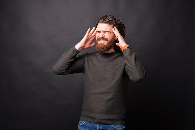 黒の背景の上に頭を抱えている欲求不満のひげを生やした男の写真