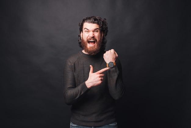 欲求不満のひげを生やした男の写真は、暗い壁を見守る
