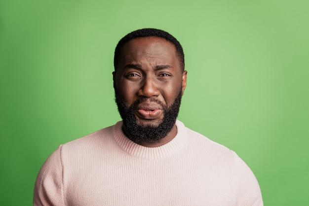 緑の背景の上に白いシャツを着て顔をしかめっ面泣いている欲求不満の絶望的な男の写真