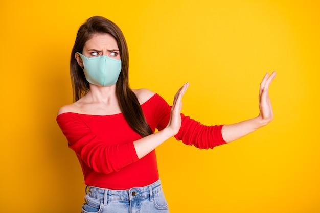 의료용 마스크를 쓴 좌절한 소녀의 사진은 밝은 색 배경 위에 격리된 빨간색 탑 데님 청바지를 입고 코비드 감염 전염병 확산을 막습니다.