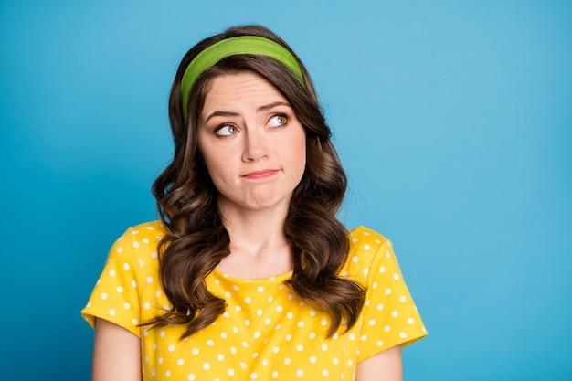 欲求不満の女の子の写真は空のスペースを見て申し訳ありませんが青い色の背景の上に分離された黄色の水玉模様の服を着ると思います