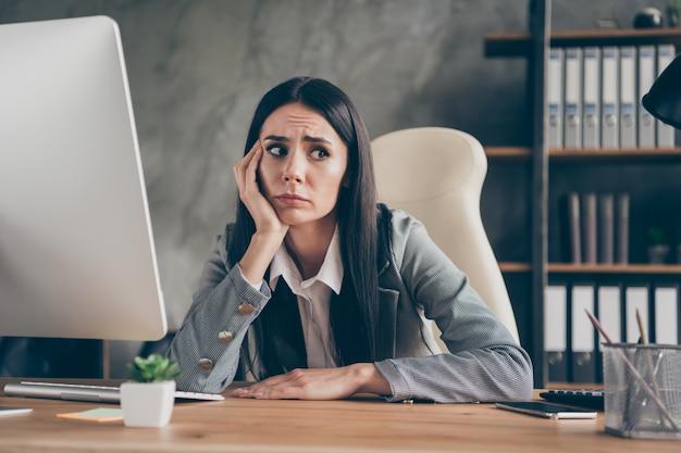 좌절한 소녀 대표 앉아 테이블 작업 원격 pc 컴퓨터의 사진은 직장 워크스테이션에서 무서운 회사 파산 직원 해고 뉴스 착용 블레이저 재킷 양복을 두려워합니다