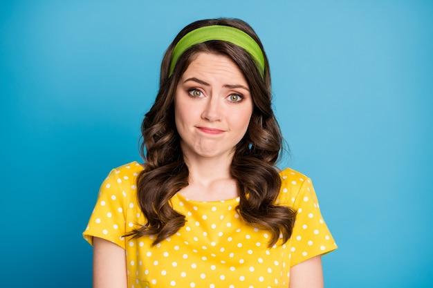 欲求不満の女の子の肩をすくめる写真は、青い色の背景の上に分離された水玉模様の服を着て申し訳ありません