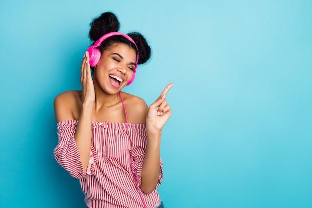 펑키 미친 어두운 피부 아가씨의 사진 음악 듣기 현대 이어폰 좋아하는 노래를 부르고 검지 손가락 착용 유행 빨간색 흰색 줄무늬 셔츠 오프 숄더 절연 파란색 벽