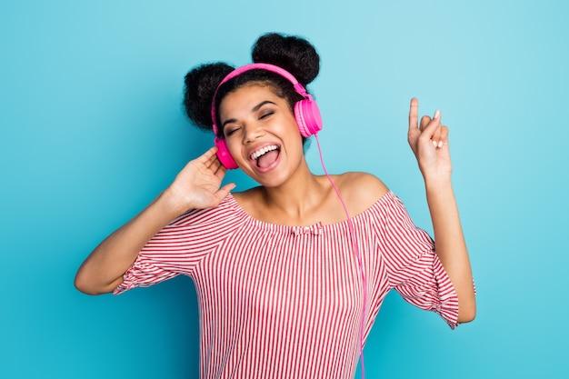 펑키 어두운 피부 아가씨의 사진 음악을 듣고 좋아하는 노래 눈을 노래하는 현대 이어폰 폐쇄 착용 유행 빨간색 흰색 줄무늬 셔츠 오프 어깨 절연 파란색 벽