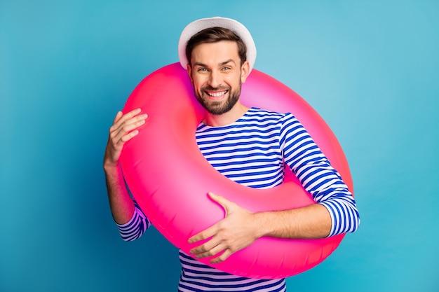 Фото напуганного красивого парня, летнего туриста, гуляющего по берегу моря, держите красочный розовый резиновый спасательный круг, время плавания, носите полосатую матросскую рубашку, кепку изолированного синего цвета