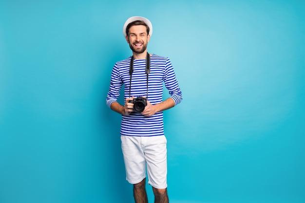 펑키 잘 생긴 남자 관광의 사진은 해외 여행 전문 직업 디지털 카메라 사진을 입고 스트라이프 선원 셔츠 모자 반바지 절연 파란색을 착용