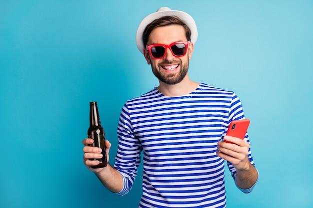 ファンキーな素敵な旅行者の男の写真ブラウジング電話ドリンクビール瓶オールインクルーシブエキゾチックリゾートウェアサンスペックストライプセーラーシャツキャップ孤立した青い色