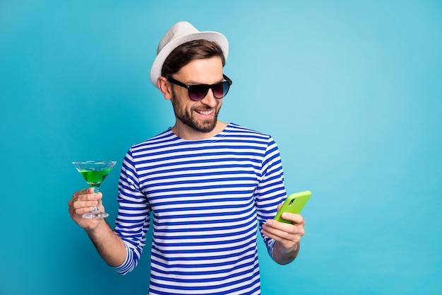 펑키 여행자 남자 검색 전화 음료 녹색 알코올 칵테일 모든 포함 이국적인 리조트 착용 태양 사양 스트라이프 선원 셔츠 모자 격리 된 파란색의 사진